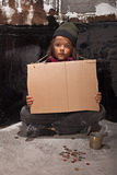 在街道上的可怜的叫化子男孩有纸板标志的 免版税库存照片