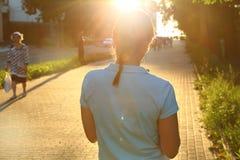 在街道上的女孩反对太阳 免版税库存照片