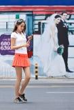 在街道上的女孩有在背景的广告牌的,昆明,中国 免版税库存照片