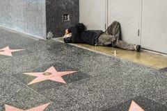 在街道上的好莱坞星光大道无家可归的人,边路 免版税库存照片