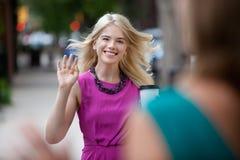 在街道上的妇女挥动的你好 免版税库存图片