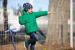 在街道上的孩子在篱芭附近站立并且显示手指某处 图库摄影