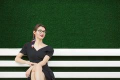 在街道上的年轻女人在一件黑夏天礼服 坐一条白色长凳 在他后是美丽的草坪 r 库存图片
