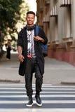 在街道上的微笑的年轻行家混合的族种人身分,举行在肩膀的一个背包和看照相机 库存照片