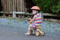 在街道上的愉快的小女孩骑马三轮车 免版税库存照片
