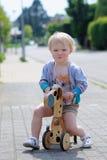 在街道上的愉快的小女孩骑马三轮车 库存照片