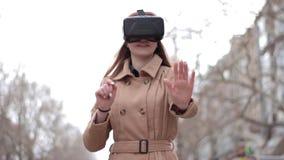 在街道上的愉快的少妇在使用米黄的外套有乐趣佩带的vr虚拟现实耳机网际空间玻璃 影视素材