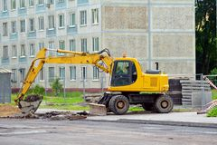在街道上的挖掘机开掘和修理路 免版税库存照片