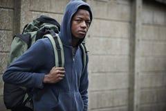 在街道上的无家可归的十几岁的男孩有背包的 免版税库存照片