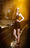 在街道上的时装模特儿有太阳镜的和短小黑色穿戴 免版税库存照片