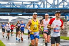 在街道上的未认出的赛跑者在16 Cracovia马拉松期间 马拉松是一次年度活动 免版税库存图片