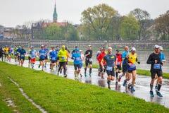 在街道上的未认出的赛跑者在16 Cracovia马拉松期间 马拉松是一次年度活动 图库摄影