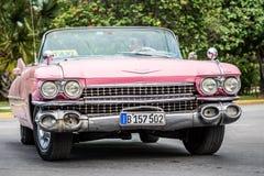 在街道上的桃红色美国经典敞蓬车汽车在圣克拉拉古巴 库存照片