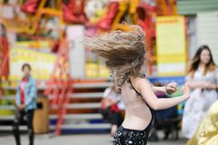 在街道上的深色的女孩跳舞 美好的白肤金发的户外,生活方式的画象一件巧妙的礼服的 免版税库存照片