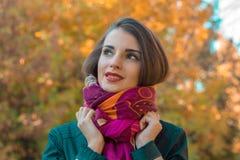 在街道上的甜女孩立场看起来去并且保留手围巾特写镜头 免版税图库摄影