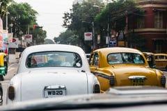 在街道上的白色和黄色经典汽车中止在加尔各答,印度 库存图片