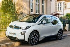在街道上的白色电杂种BMW i1汽车 免版税库存照片