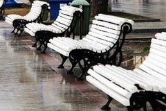 在街道上的白色长凳在雨以后的堤防附近 库存照片