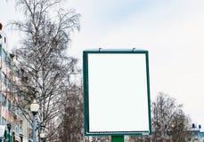 在街道上的空白的广告牌在背景树和天空,冬天都市风景, 库存图片