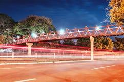 在街道上的红色步行桥在晚上 库存图片