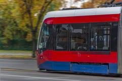 在街道上的红色现代公开电子铁路电车有森林的 库存照片