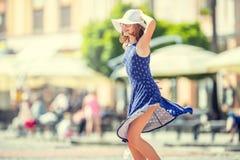 在街道上的美好的逗人喜爱的女孩跳舞从幸福 逗人喜爱的愉快的女孩在夏天给跳舞穿衣在阳光下 免版税库存图片