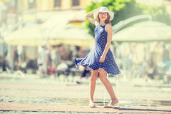在街道上的美好的逗人喜爱的女孩跳舞从幸福 逗人喜爱的愉快的女孩在夏天给跳舞穿衣在阳光下 库存照片