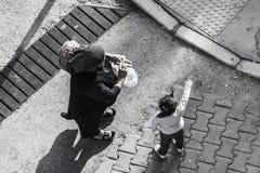 在街道上的老土耳其妇女有孩子的 库存照片