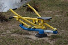 在街道上的色的金属体育模拟器在江边的绿草 免版税库存图片