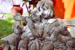 在街道上的艺术对象:愉快的孩子雕塑有一条狗的在长凳 库存图片