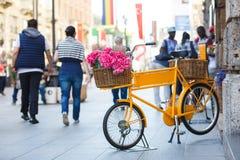 在街道上的葡萄酒黄色自行车 库存照片
