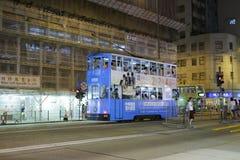 在街道上的蓝色电车轨道公共汽车在晚上 免版税库存图片