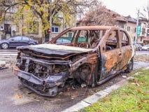 在街道上的被放弃的被破坏的被烧的汽车 免版税图库摄影
