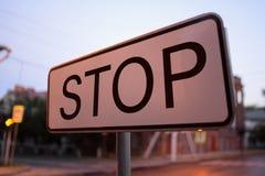 在街道上的路标中止在晚上 金属在路登上的街道杆 与题字中止的交通标志 库存照片