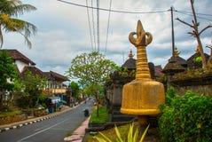 在街道上的金黄stupa在Ubud,巴厘岛,印度尼西亚 免版税图库摄影