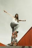 在街道上的青少年的女孩溜冰者骑马滑板 库存图片