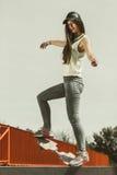 在街道上的青少年的女孩溜冰者骑马滑板 免版税库存照片