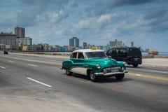 在街道上的经典美国汽车驱动在哈瓦那,古巴 免版税库存照片