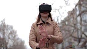 在街道上的年轻愉快的女孩在使用米黄的外套有乐趣佩带的vr虚拟现实耳机网际空间玻璃 股票视频