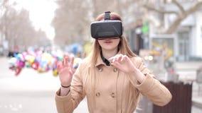 在街道上的年轻愉快的妇女在使用米黄的外套有乐趣佩带的vr虚拟现实耳机网际空间玻璃 股票视频