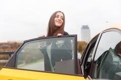 在街道上的年轻深色的身分在门户开放主义的出租汽车 免版税库存图片