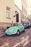 在街道上的绿色大众甲壳虫 图库摄影