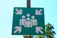 在街道上的绿色集合点标志 免版税库存图片