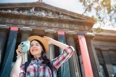 在街道和微笑上的有吸引力的年轻女性旅行家立场 Sheholds在手边在帽子 另一个有蓝色照相机 她 免版税库存照片
