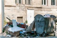 在街道和破烂物倾销的大堆垃圾在大型垃圾桶罐头附近 免版税库存图片