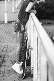 在街道和滑板上的少妇 图库摄影