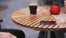 在街道咖啡馆桌上的手机 库存图片