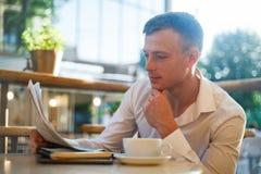 读在街道咖啡馆的体贴的人一张报纸在午餐 免版税图库摄影