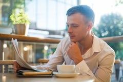 读在街道咖啡馆的体贴的人一张报纸在午餐 免版税库存照片