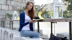 在街道咖啡馆的年轻愉快的妇女读书菜单 影视素材